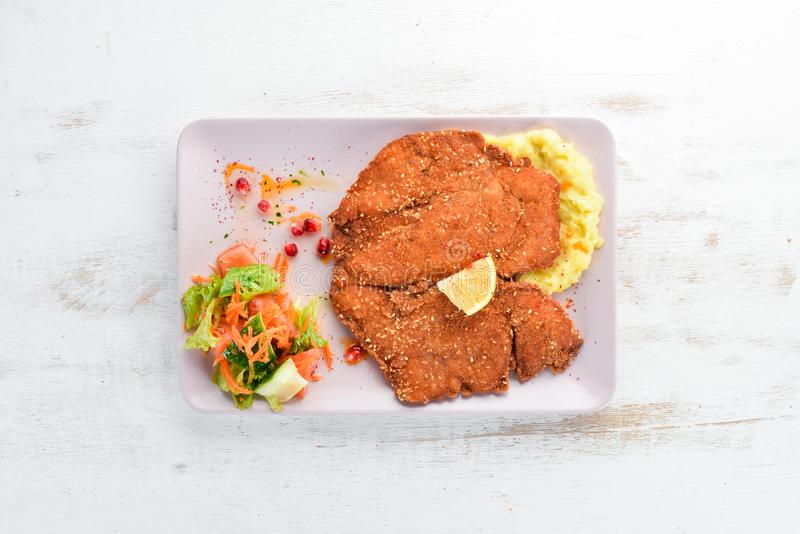 Chicken schnitzel with mashed potatoes on a plate. On a wooden background. stock photo