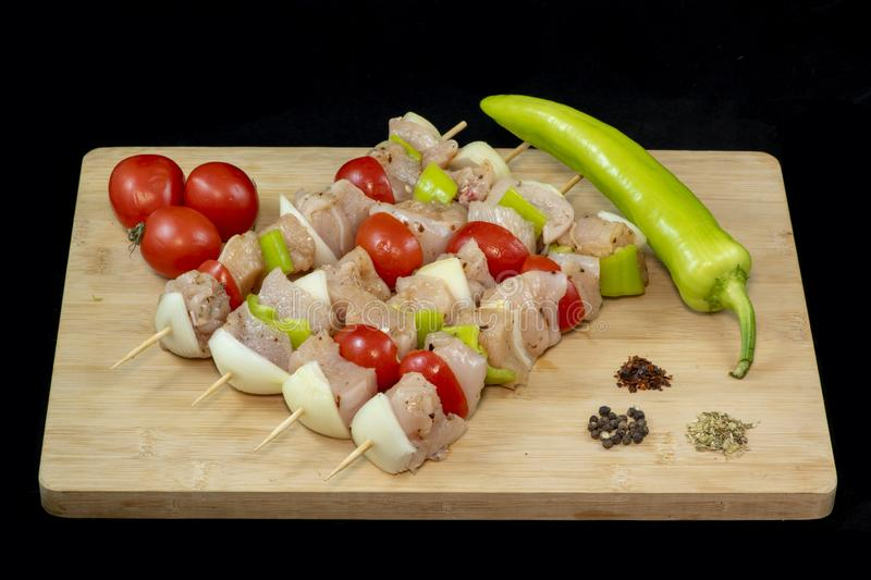 Chicken Shish Kebab with tomato, onion and green peppers on wood stock image