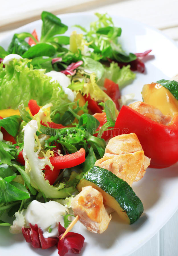 Chicken skewer with salad mix stock photography