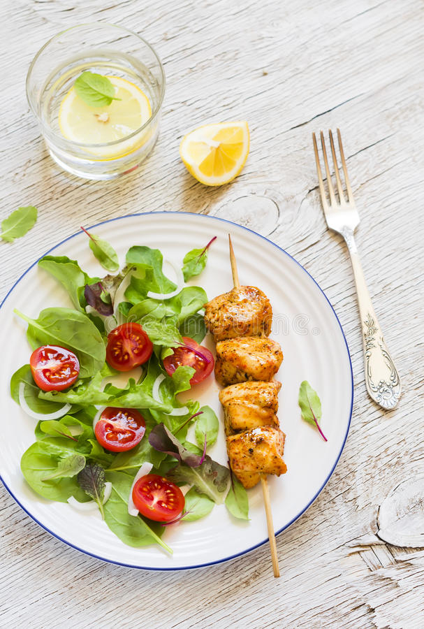 Chicken skewers and fresh vegetable salad with cherry tomatoes and spinach. On a light wooden background royalty free stock photo