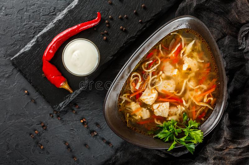 Chicken soup with broth with noodles, herbs, pepper and vegetables in bowl on black stone background. Healthy food, top view royalty free stock photo