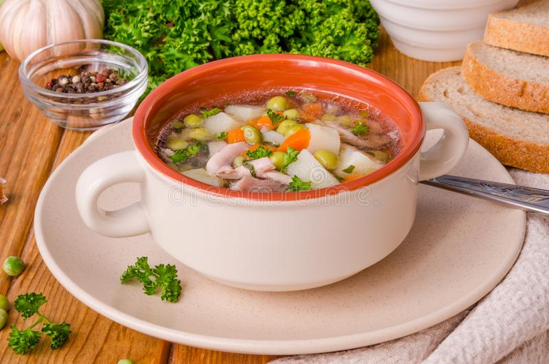 Chicken soup with green peas and vegetables in a bowl. On a wooden background royalty free stock photos