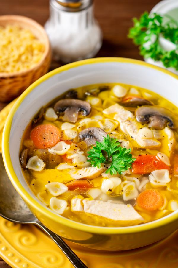 Chicken soup with mushrooms, vegetables and pasta in bowl on wooden table. stock image