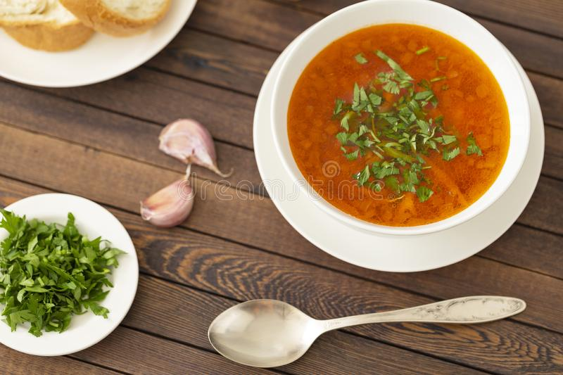 Chicken soup with vegetables and herbs in a white bowl. On a wooden table stock photography