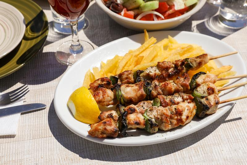Chicken souvlaki cooked on grill served with french fries, half of lemon in greek tavern. stock images