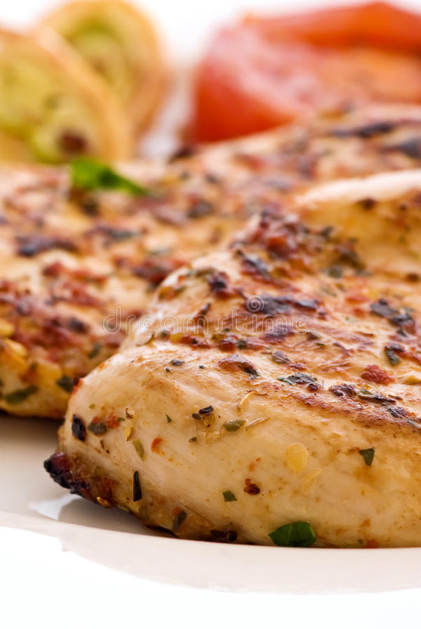 Chicken Steak. Spicy chicken steak with vegetables as closeup on a plate stock images