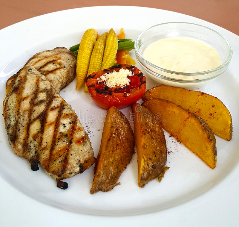 Chicken Steak and Potato Wedges. Asian style chicken steak with potato wedges, stirfried vegetables and mayonnaise royalty free stock photo