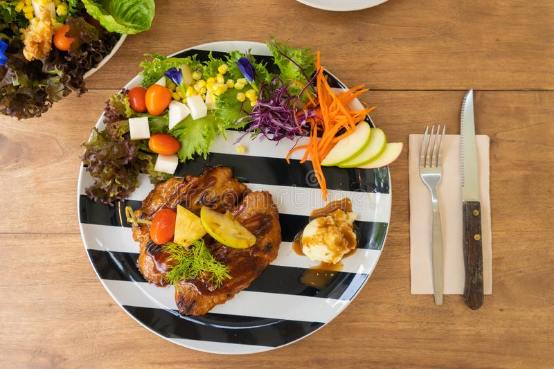Chicken steak serve with mashed potato and salad on a black and white plate on a wooden table stock images