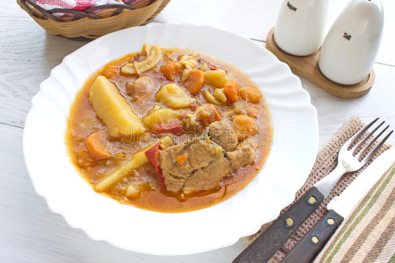 Chicken stew with potatoes in plate. On white table stock image