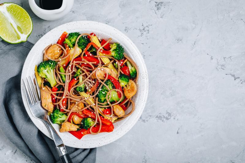 Chicken stir fry noodles bowl with broccoli royalty free stock image