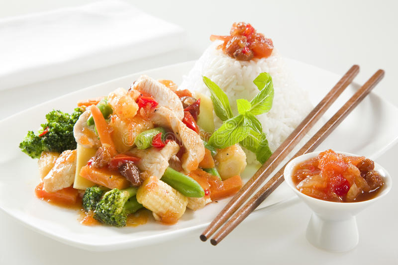 CHICKEN STIR FRY WITH RICE. Chicken stir fry with chutney SERVED ON CONTEMPORARY CROCKERY WITH WOODEN CHOPSTICKS royalty free stock photo