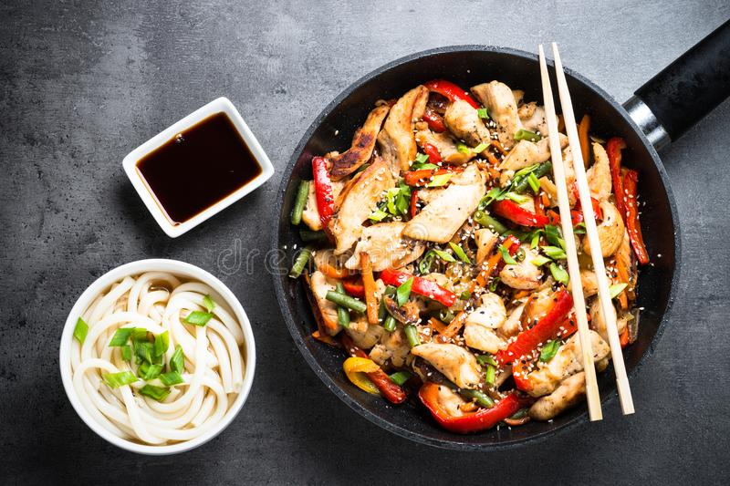Chicken Stir fry and udon noodles on black. Chicken Stir fry and udon noodles on black slate table. Traditional asian food. Top view copy space royalty free stock photo