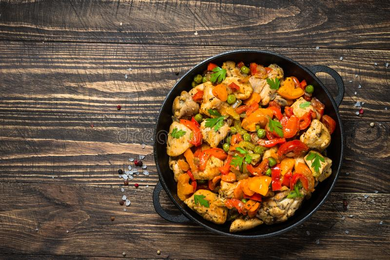Chicken Stir fry with vegetables on wooden table. royalty free stock photo