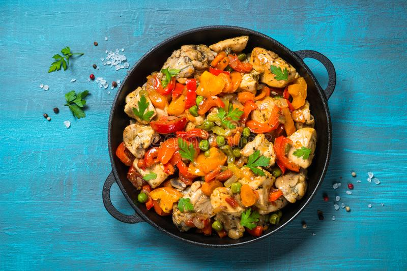 Chicken Stir fry with vegetables on blue table. stock image
