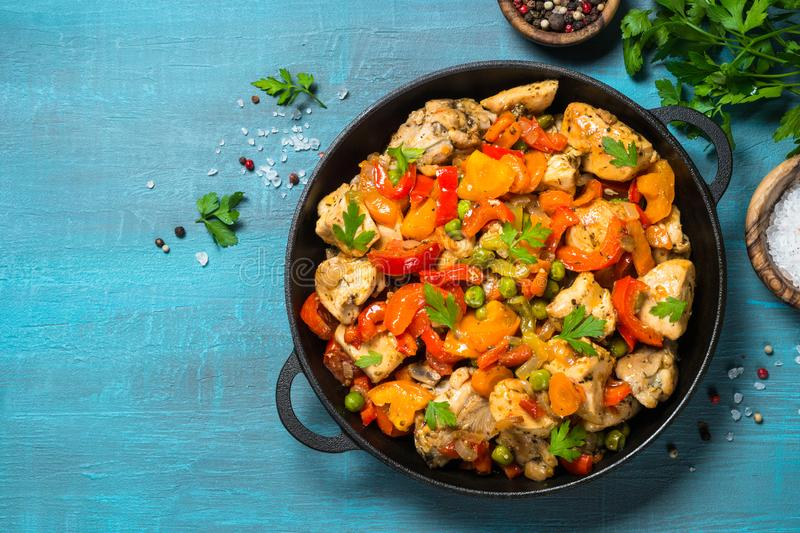 Chicken Stir fry with vegetables on blue table. stock photo