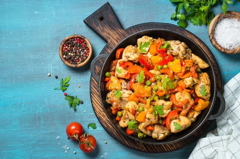 Chicken Stir fry with vegetables on blue table. royalty free stock photo