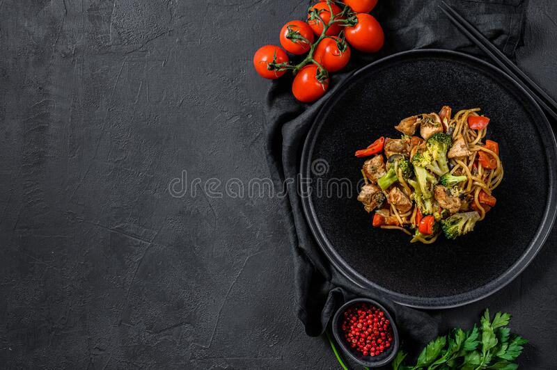 Chicken stir fry with vegetables soy sause, wok. Traditional asian food. stone black table.  stock images