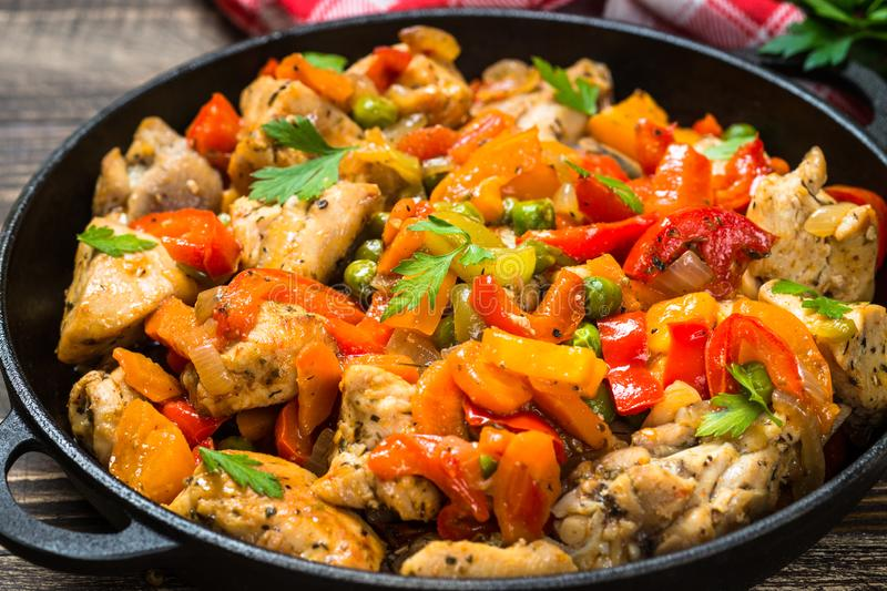 Chicken Stir fry with vegetables on wooden table. royalty free stock photography