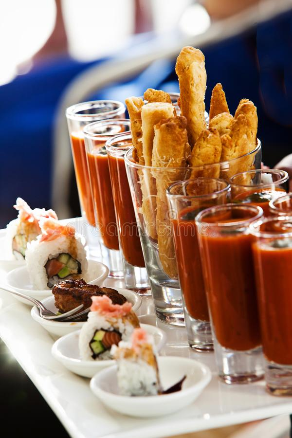 Chicken Strips with Shooter chilli tomato sushi California rolls. A tray with amazing finger food. Petite four, with california spring rolls and sushi royalty free stock photos