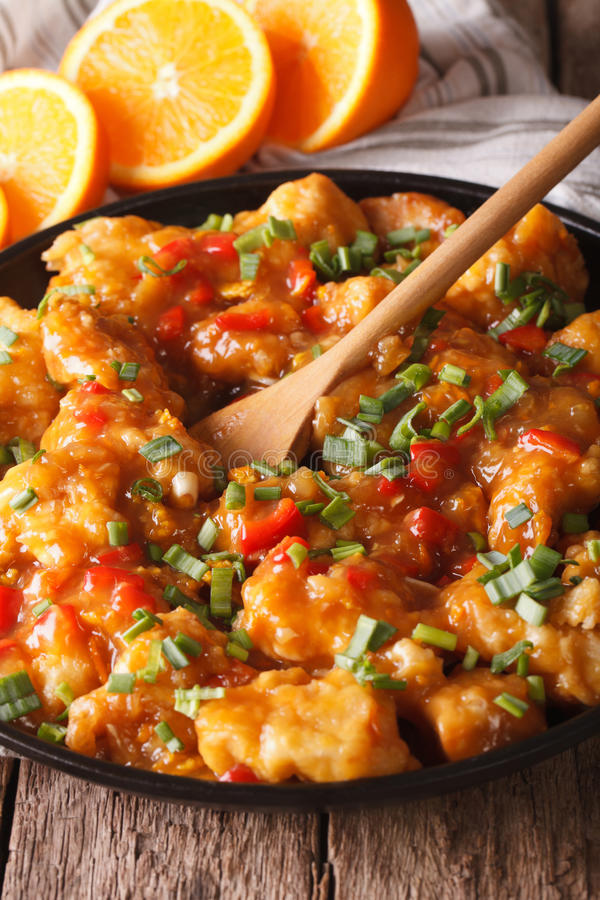 Chicken in sweet and sour orange sauce closeup. vertical royalty free stock image