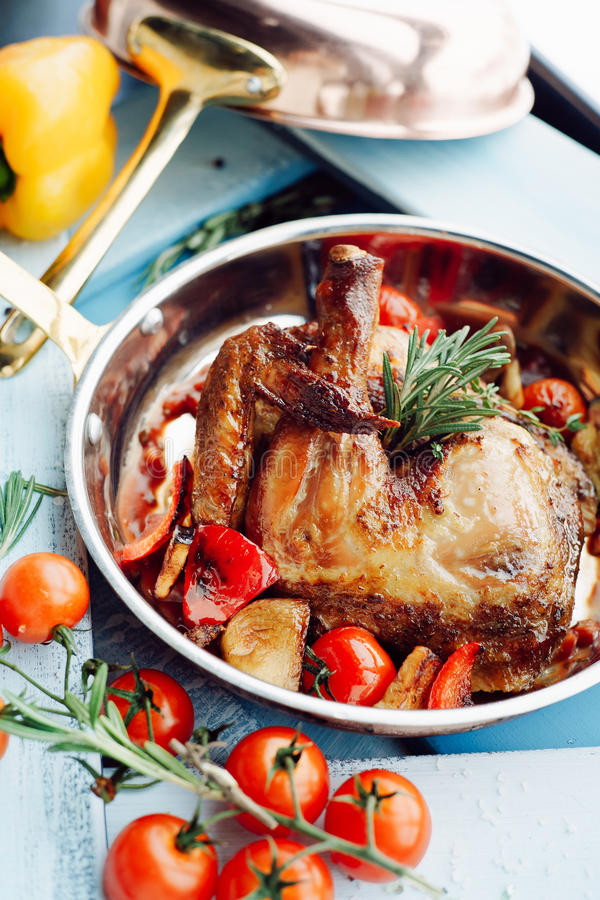 Chicken Tabaka in a pan with vegetables and tomatoes stock images