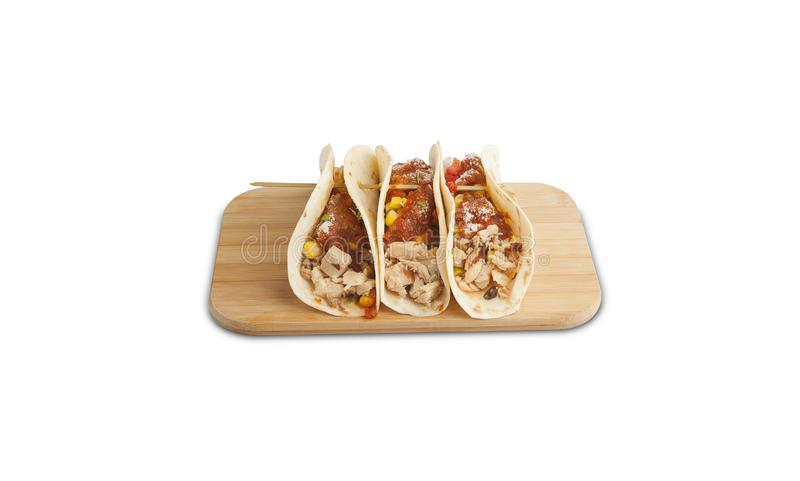 Chicken tacos on a wooden board isolated on a white background royalty free stock photos