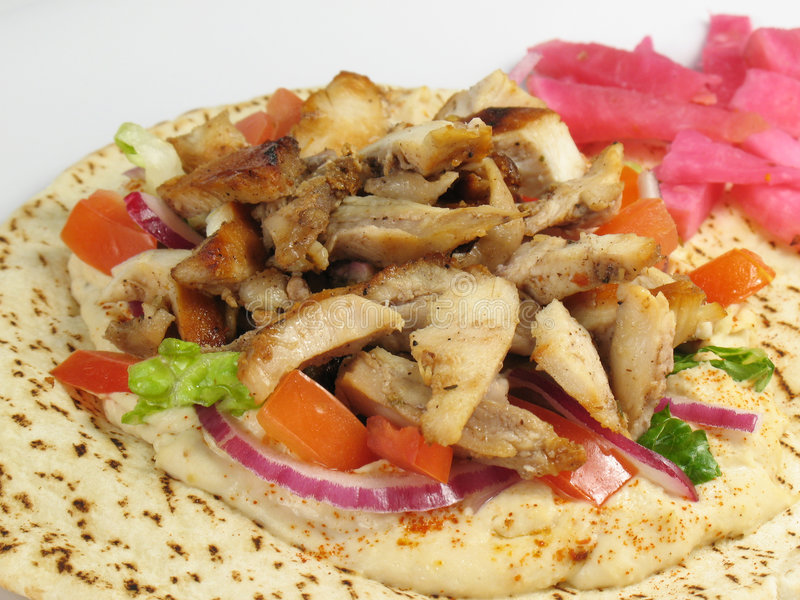 Chicken Tarna With Hummus. Shawarma style chicken tarna on a pita, with hummus, lettuce, tomato, red onions, and a side of turnips pickled in beet roots stock photos