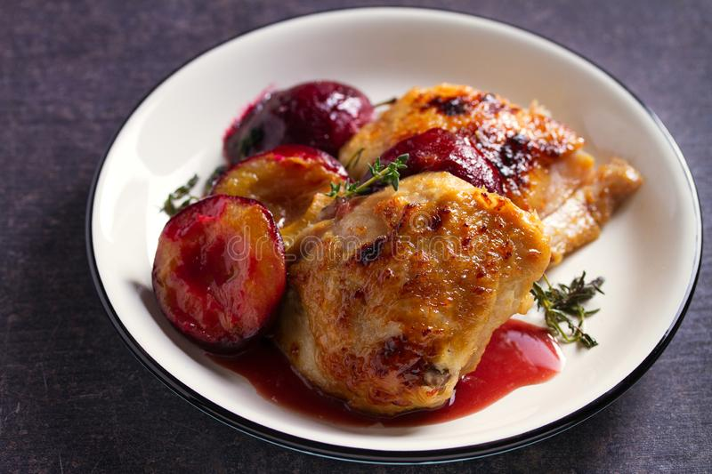 Chicken thighs and plums in ginger, honey and red wine sauce with thyme. royalty free stock images