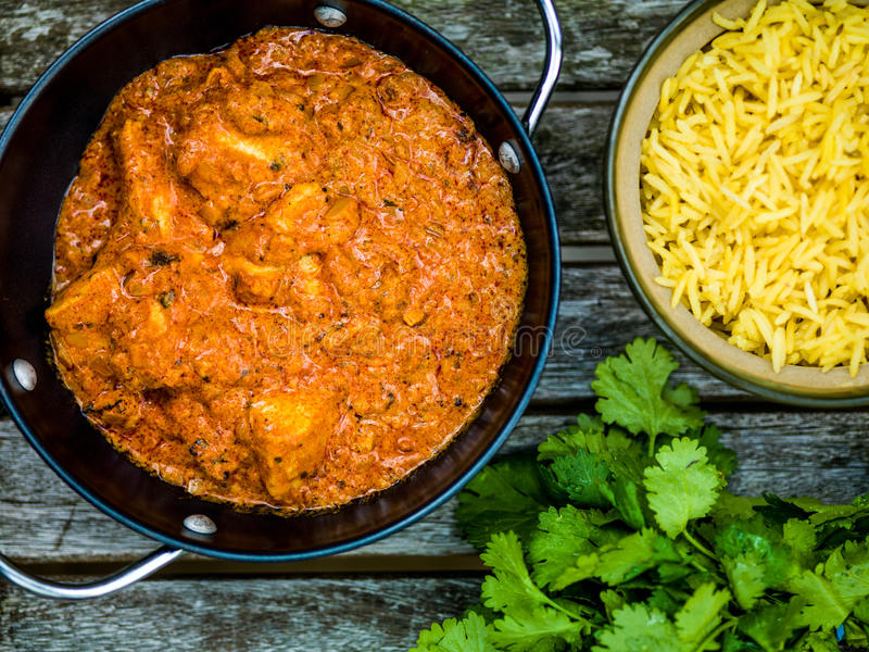 Chicken Tikka Masala Indian Takeaway Curry With Pillau Rice. Against a Dark Wooden Background royalty free stock image