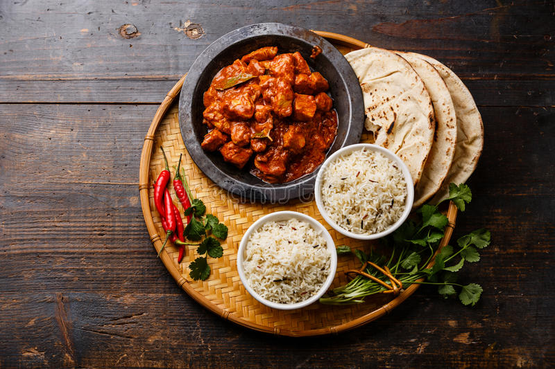 Chicken tikka masala with rice and naan bread. Chicken tikka masala spicy curry meat food with rice and naan bread on wooden background stock images