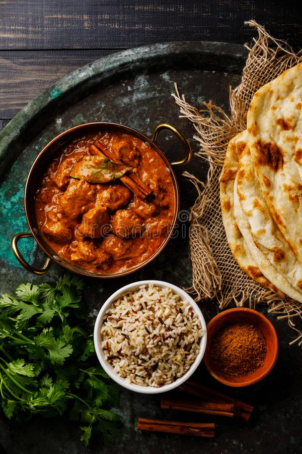 Chicken tikka masala spicy curry meat food with rice. And naan bread on dark background stock photography