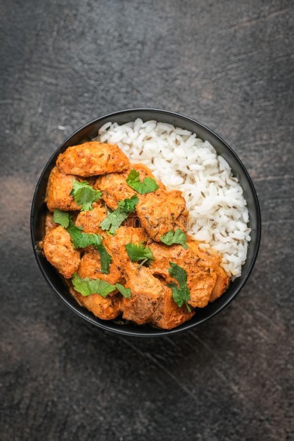 Chicken tikka masala traditional Asian spicy meat food. With rice tomatoes and cilantro in a black bowl on dark background. Top view royalty free stock image