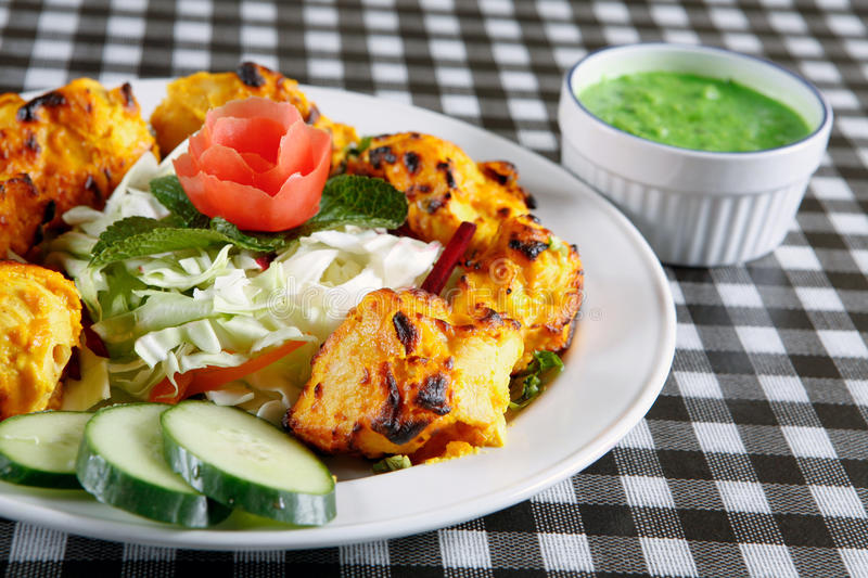 Chicken tikka with salad and sauce. Hot and spicy tandoori chicken tikka for snack time at restaurant stock photo