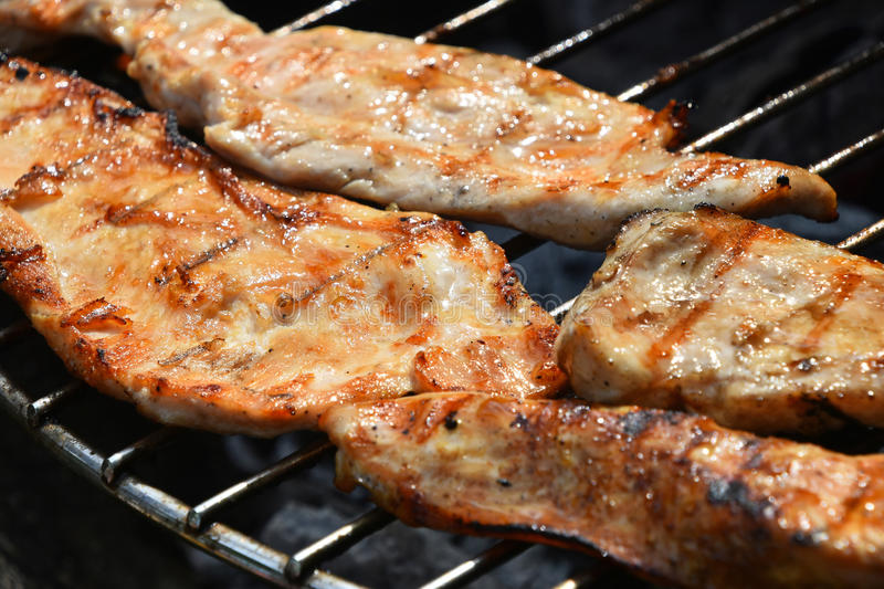 Chicken or turkey steak ready cooked on grill. Chicken or turkey meat barbecue steak ready cooked grilled on bbq smoke grill, close up stock photos