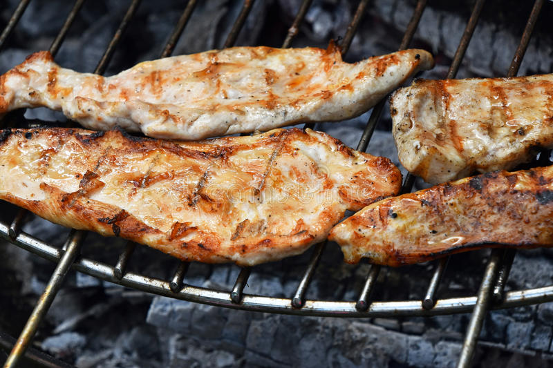 Chicken or turkey steak ready cooked on grill. Chicken or turkey meat barbecue steak ready cooked grilled on bbq smoke round grill, close up royalty free stock photo