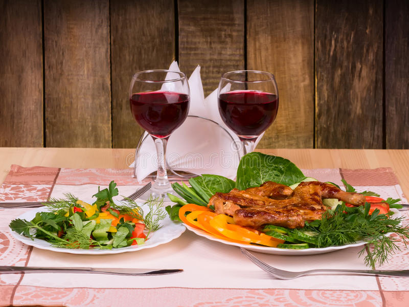 Chicken with vegetables and salad with two glasses of red wine. Grilled chicken with vegetables and salad and glasses of red wine on table in wooden restaurant stock photo