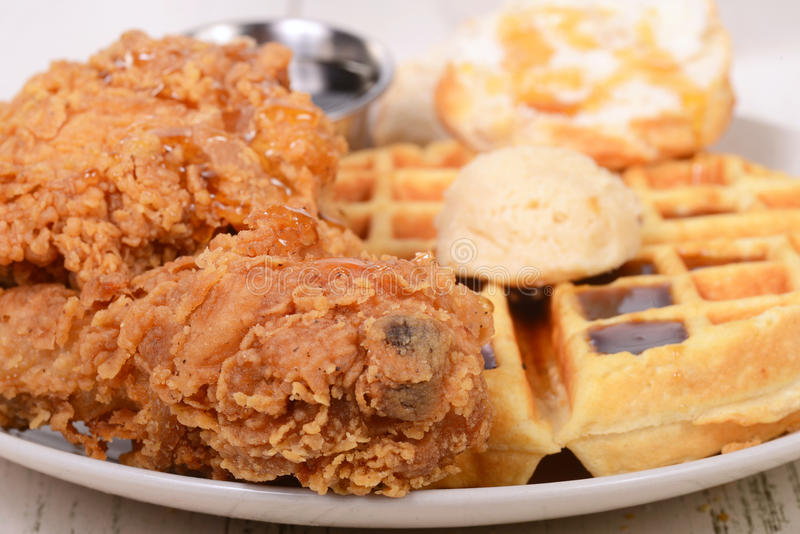Chicken and Waffles with a biscuit. Closeup of Chicken and Waffles with honey, maple butter and maple syrup royalty free stock photos