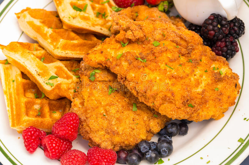 Chicken and Waffles. Popular southern dish of fried breaded chicken with waffles, served with berries and maple syrup stock photography