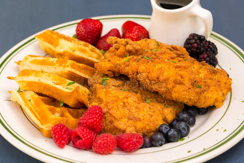 Chicken and Waffles. Popular southern dish of fried breaded chicken with waffles, served with berries and maple syrup royalty free stock photo