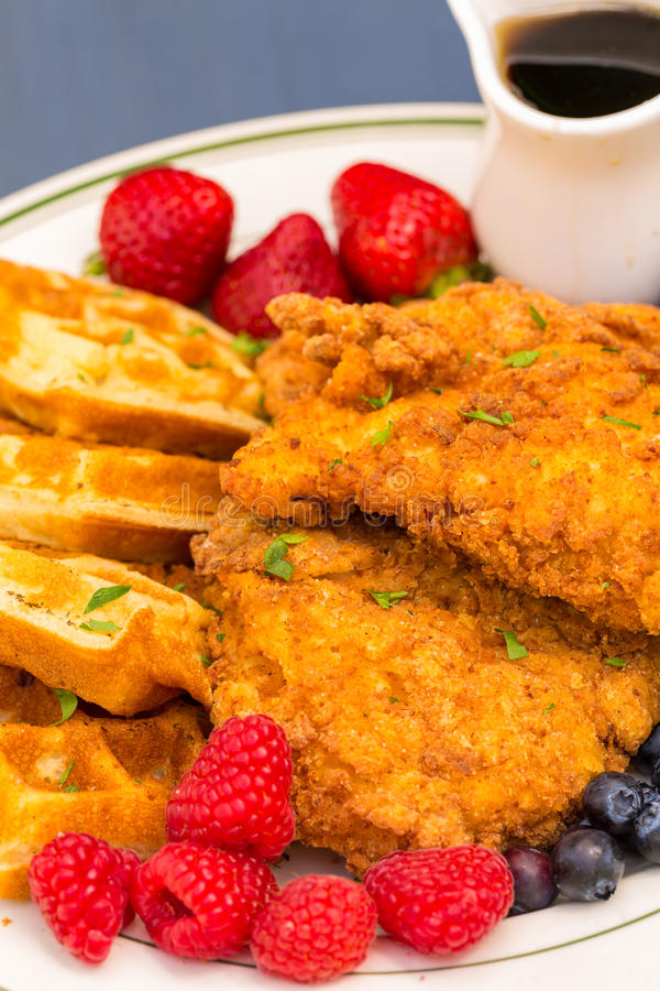 Chicken and Waffles. Popular southern dish of fried breaded chicken with waffles, served with berries and maple syrup royalty free stock photos
