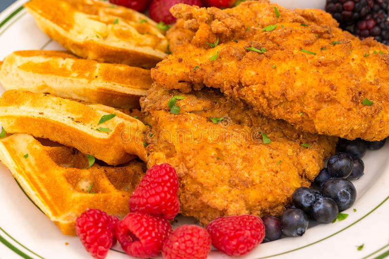 Chicken and Waffles. Popular southern dish of fried breaded chicken with waffles, served with berries and maple syrup royalty free stock images