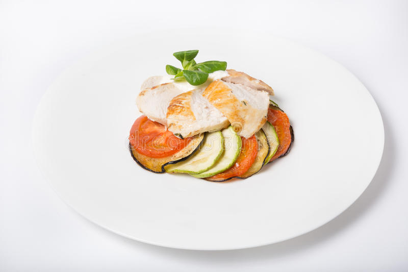 Chicken white meat with ratatouille garnish. On plate royalty free stock image