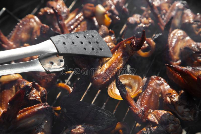 Chicken wing hold in nippers, smoked, on barbecue grill stock photo