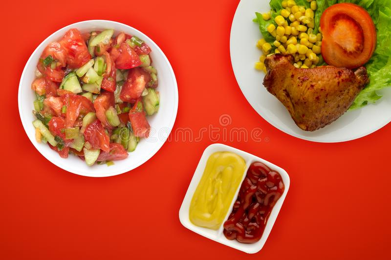 Chicken wing with lettuce, corn and tomatoes on a white plate. chicken wing with vegetable salad and sauce on a background top royalty free stock images