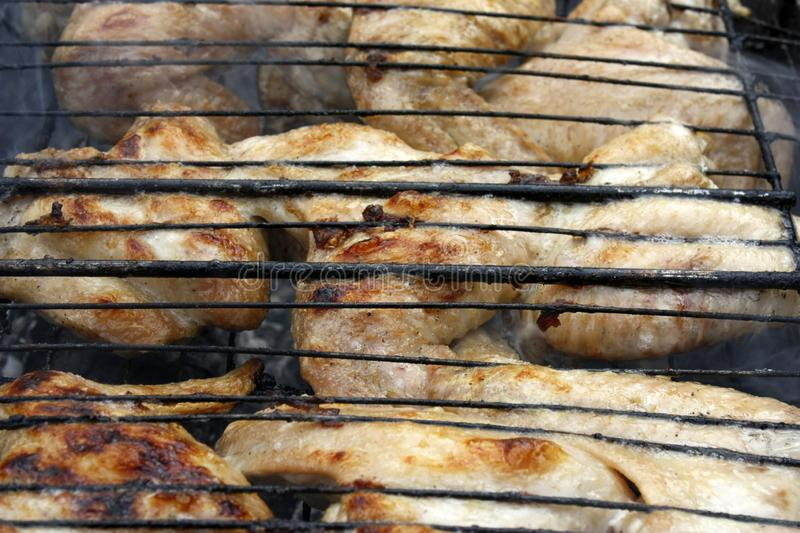 Chicken wings on barbecue grill with fire smoking. Chicken wings on barbecue grill with fire smokin. BBQ cooking food grilled meat hot delicious grilling meal royalty free stock photo