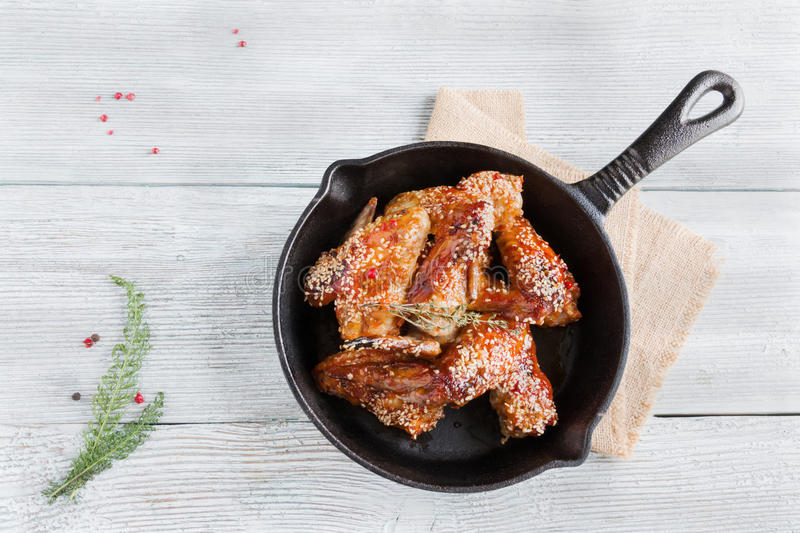 Chicken wings in cast-iron pan. Marinated in tomato and honey sauce. Baked with sesame seeds. Top view, wooden table royalty free stock image