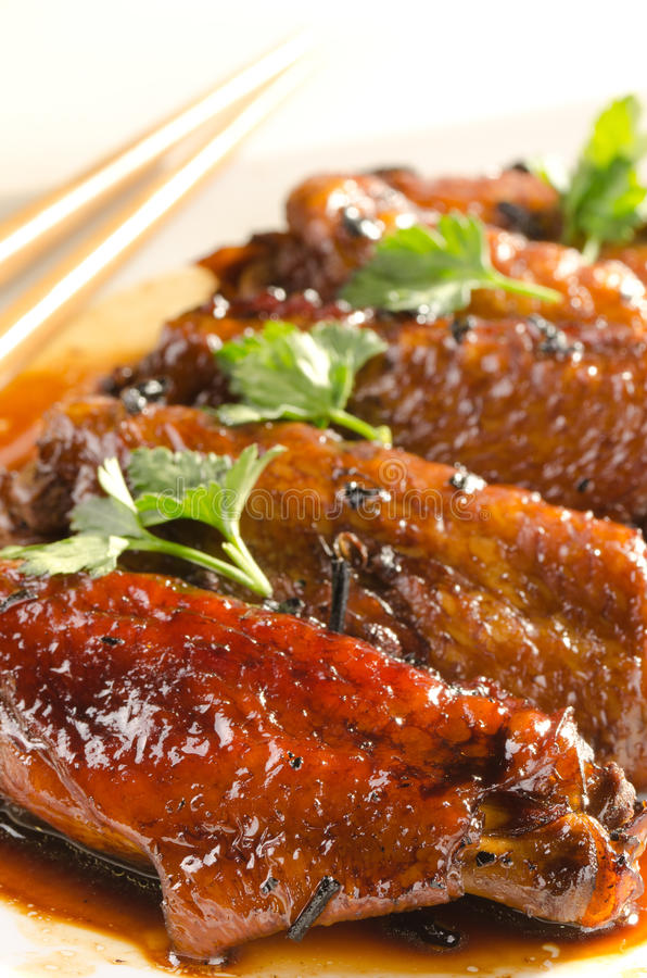 Chicken wings in chinese sauce with puer tea and h. Erbs stock photos