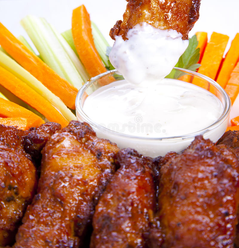 Chicken wings detail. Deep-fried Buffalo chicken wings in cream cheese dip royalty free stock photo