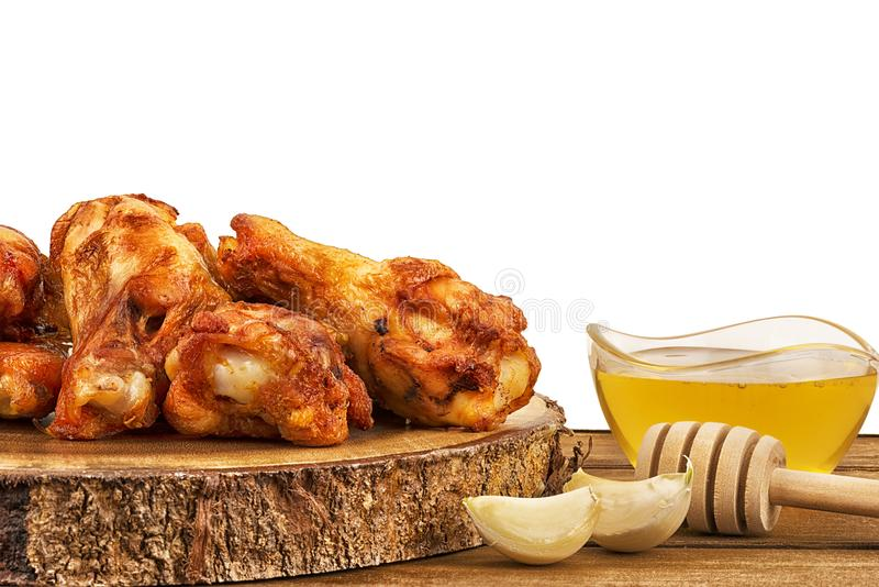 Chicken wings with garlic cloves and a bowl of fresh honey on wooden table. stock photography