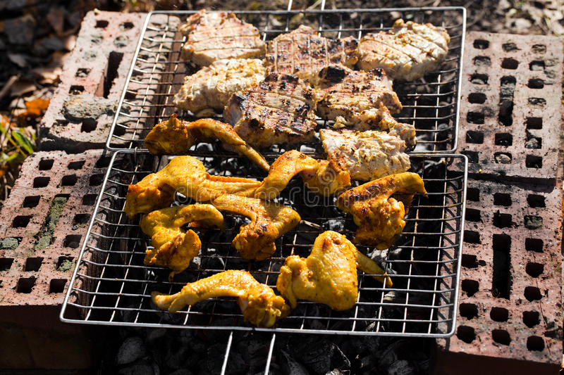 Chicken wings on the grill and pork